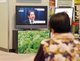 28日の衆院解散を表明した安倍晋三首相の会見で、テレビ中継に見入る女性=25日夕、佐賀市川副町の佐賀空港