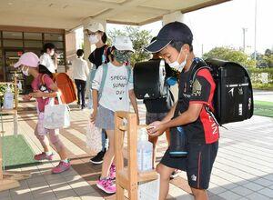 マスクを着用し、入り口で手を消毒して校舎に入る児童ら=31日朝、佐賀市の赤松小(撮影・山田宏一郎)