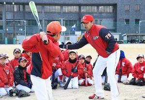 ボールの弾道を意識させながらスイングを教える広島の緒方監督(中央)=神埼中央公園