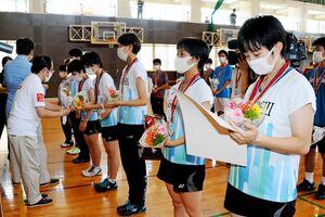 バドミントン女子団体で優勝し、賞状やメダルとともに花束を受け取る佐賀女子のメンバー=佐賀市の旭学園体育館