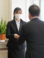 決定通知書を受け取る、奨学生の石丸凪海さん=佐賀市の西九州大学短大