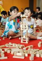 ヒノキの匂いが漂う中、夢中になって積み木で遊ぶ子どもたち=佐賀市立図書館