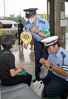 町民の靴に反射シールを貼ったり、ニセ電話詐欺への注意を呼び掛けたりする警察官=吉野ヶ里町健康福祉センター「きらら館」