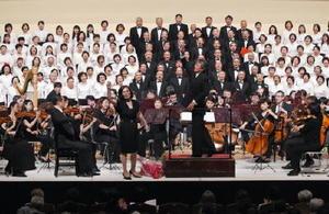 合唱組曲「唐津」を披露した市民合唱団。ステージの最後、合唱指導者の永富啓子さん(中央左)が小泉和裕さんと客席に向かって指揮し、客席も一体となって歌声を響かせた=唐津市民会館