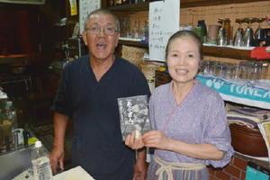 評伝を手にする永渕さん(左)と妻の正江さん=佐賀市の焼き鳥店「あぶさん」