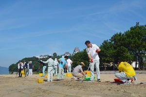 浜に漂着した流竹木を重機で撤去した後、木ぎれを拾い集める唐津市職員=唐津市西の浜