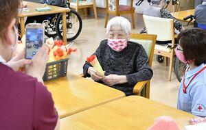 手作りのカーネーションの造花を手に、家族へ送る動画を撮影する利用者=佐賀市本庄の有料老人ホーム「SINみらい」
