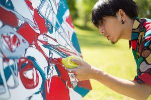 アール・ブリュット(生の芸術)を提唱した「ジャン・デュビュッフェ」のオブジェ前でライブペイントをする冨永ボンドさん=6月、パリ(撮影:Yusuke Hirashima)