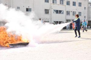 消火器を使って火を消す参加者=佐賀市の佐賀広域消防局