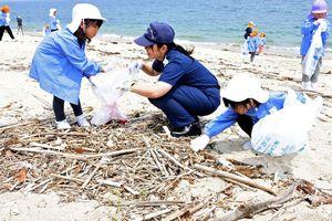 海上保安官と一緒にごみ拾いをする園児たち=唐津市の東の浜海水浴場