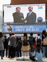 板門店での北朝鮮の金正恩朝鮮労働党委員長と韓国の文在寅大統領の握手を生中継で伝えるモニターを見る人たち=27日、ソウル(共同)