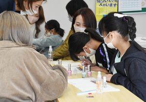サポートを受け、ネイルを体験する参加者=佐賀市唐人のエッジ国際美容専門学校