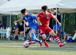サイドライン際でボールを奪い合う佐賀大(左)とEVインテルナシオナルの両選手=唐津市の佐賀県フットボールセンター