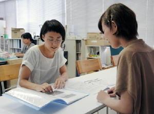 大会ボランティアについて、資料を使いながら丁寧に説明する佐賀市の田中さん(左)=佐賀市の熱気球世界選手権推進室
