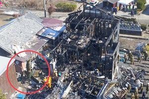 陸上自衛隊のAH64D戦闘ヘリが墜落、住宅が炎上した現場で、早朝から続く検証作業。左下には機体後部とみられる残骸が見える(赤丸内)=6日午前11時ごろ、神埼市千代田町(小型無人機ドローンで撮影)