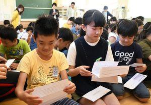 マレーシアの子どもたちから返事の手紙をもらいうれしそうな児童=佐賀市の開成小
