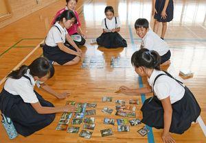 地域の名所を題材にした「金立郷土かるた」で遊ぶ児童=佐賀市の金立小