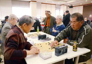 真剣な表情で碁盤を見つめ、石を打つ参加者たち=佐賀市の佐賀新聞社