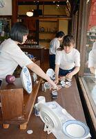 焼き物などの配置を慎重に考える牛津高の生徒たち=有田町幸平の手塚商店