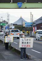 メッセージボードを掲げて啓発する関係者=杵島郡白石町の国道207号沿線