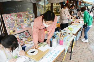 どんぐりキッズ市場で絵手紙体験の講師を務めた子どもたち。手作り雑貨などが並び、大人による菓子やパンの販売もあった=佐賀市三瀬村のどんぐり村