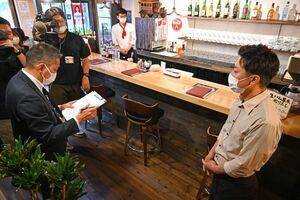 調査員(左)の質問に答える「洋風バル サガんチーノ」の今田篤人さん(右)=佐賀市白山