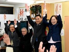 当選が確実となり、支援者とともに万歳三唱する峰達郎さん(右から2人目)。右は妻・晃子さん=29日午後10時41分、唐津市町田の事務所