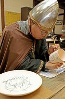 「ヴィンランド・サガ」のキャラクターを絵付けする幸村誠さん=有田ポーセリンパーク