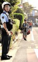 通学路で取り締まりを行う警察官=佐賀市の鍋島小付近