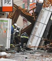 爆発のあった建物付近を調べる消防隊員ら=17日午前8時14分、札幌市豊平区
