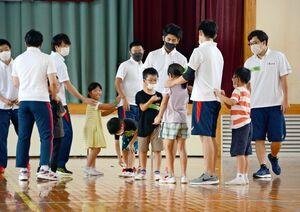 児童とじゃんけん列車に興じる大学生ら=神埼市の西郷小体育館