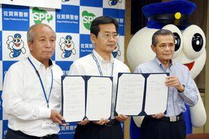 覚書を締結した県警生活安全部の石橋憲茂部長(中央)。左は堤理事長、右は中越理事長=佐賀県警本部