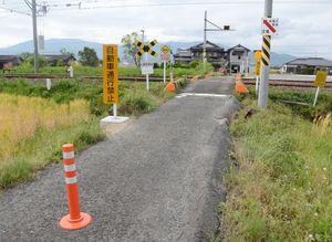 昨年6月に死亡事故が起きた於保踏切。自動車通行が禁止となり、看板やポールが設置された=小城市三日月町