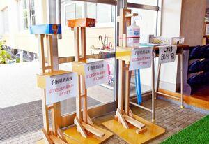 足踏み式の手作りスタンド。利用者の身長に合わせて、消毒液を置く高さを調整できる