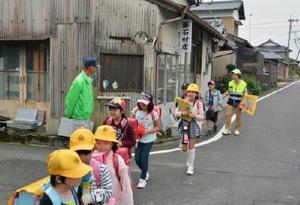 声を掛けながら登校中の小学生と一緒に歩く「見守り隊」のメンバー=有田町の大山小近く