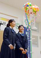 来館30万人目を祝うくす玉を割り、笑顔を見せる馬渡真衣さん(右)と下田真由さん=佐賀市青少年センター