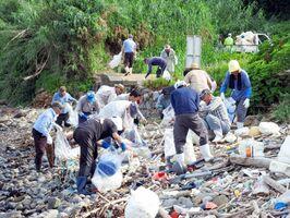 加部島で「玄海クリーンアップ作戦」の清掃活動に励む参加者=唐津市呼子町(県提供)