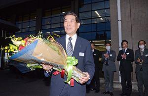 職員から受け取った花束を手に塩田庁舎を後にする谷口太一郎市長=2日、嬉野市役所