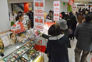 食品コーナーで福袋やセール品を購入する買い物客=2日、佐賀市の佐賀玉屋