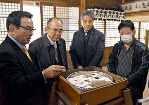 お粥のカビの付具合を確認する秀島市長(左から2人目)や地元住民=佐賀市川副町の海童神社