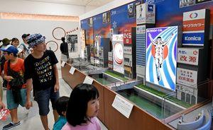 1935年の初代から現在の6代目まで、大阪道頓堀にあるグリコのネオンサインの歴代ジオラマが並ぶ=佐賀市の県立美術館