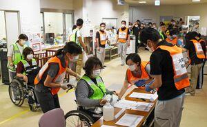 避難所運営訓練で障害のある人の受け付けを行う職員=大町町の総合福祉センター