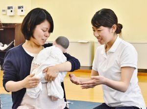 赤ちゃんの人形を使って抱っこの仕方を学生に教わる参加者=佐賀市の鍋島公民館