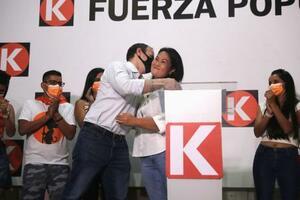 11日、ペルーの首都リマの所属政党本部で、演説中に夫と抱き合うケイコ・フジモリ氏(中央)(ロイター=共同)