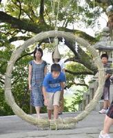 無病息災を願い、大きな茅の輪をくぐる参拝者たち=みやき町白壁の千栗八幡宮