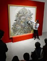 大作「興亡史」の前で絵の説明をする池田学さん=佐賀市の県立美術館