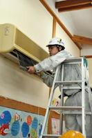 冷暖房機器のフィルターを清掃する組合員=小城市三日月町