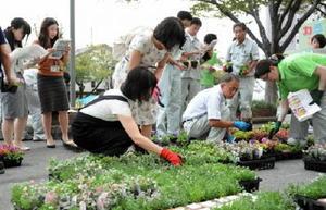 色とりどりの花苗を使ってバルーンの絵を作る作業に取り組む参加者=佐賀市役所南の駐車場