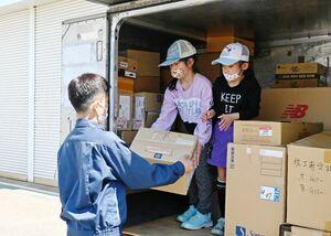 北陵高の生徒から段ボールを受け取り、積み荷体験をする子どもたち=佐賀市の同校