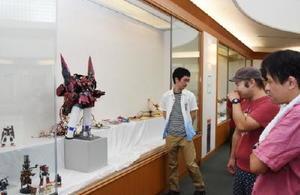 軍艦、戦車、クラシックカーのほかアニメのロボットなど、世代やジャンルを超えた多彩な作品が並ぶ展示会=佐賀市立図書館